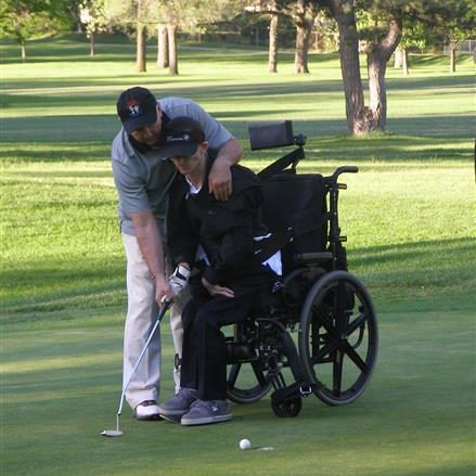 Coach with special needs student on putting green